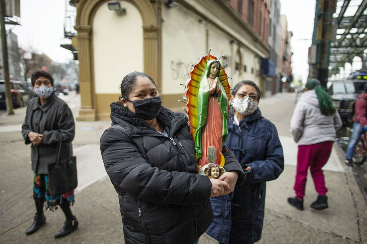 In this Dec. 12, 2020 file photo, Mexican migrants carry a statue of the Virgin of Guadalupe in Brooklyn, New York. The Hispanic community in the U.S. has been one of the groups most affected by the COVID-19 pandemic.