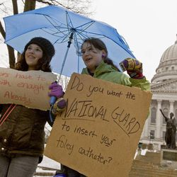 Jane Moran, left, 14, and Emma Rankin-Utevsky, 14, protest outside of at the State Capitol in Madison, Wis., Sunday, Feb. 20, 2011. Opponents to the governor's bill to eliminate collective bargaining rights for many state workers are on their sixth day of protesting.