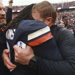 Virginia head coach Bronco Mendenhall, right, buries his head in the shoulder of Virginia quarterback Bryce Perkins (3) as he and his team celebrate beating Virginia Tech after an NCAA college football game between Virginia Tech and Virginia in Charlottesville, Va., Friday, Nov. 29, 2019. Virginia defeated Virginia Tech 39-30 for the first time in 15 years.