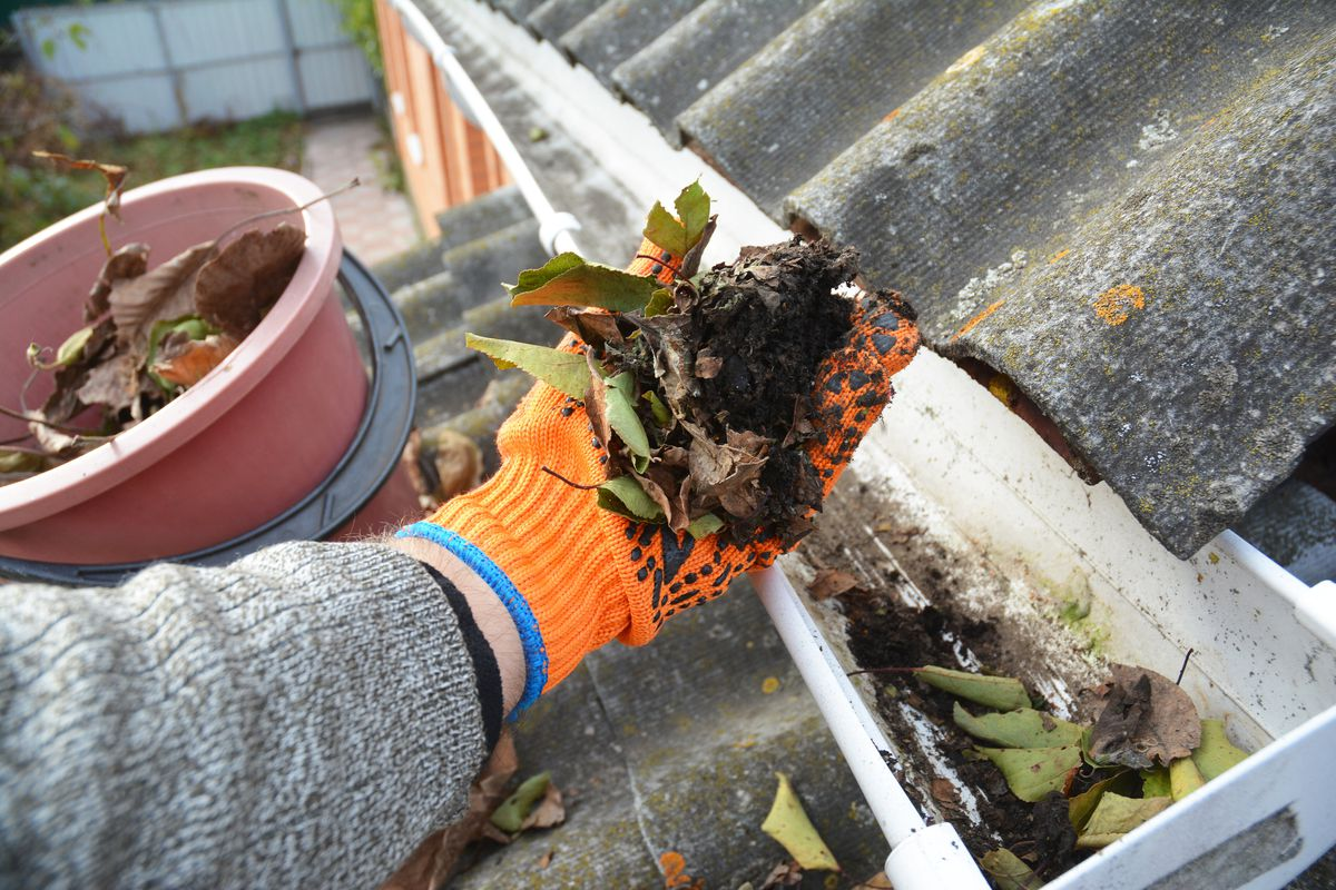A professional wearing a grey jacket and orange gloves scoops dirt and leaves out of a home's gutter.