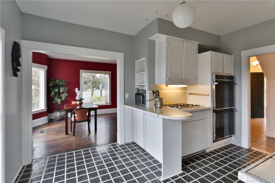 A kitchen with black tile and white grout, gray walls, and white trim and cabinetry. A wide, open doorway leads to a hardwood floor dining room with deep red walls.