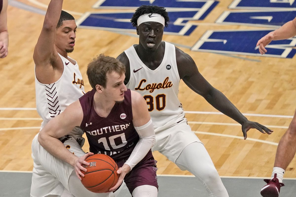 Southern Illinois' Ben Harvey (10) looks to pass as Loyola of Chicago's Lucas Williamson, left, and Aher Uguak (30) defend during the first half of Friday's MVC tournament game in St. Louis.
