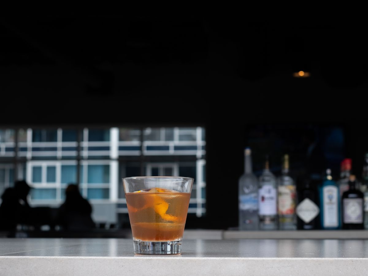 An old fashioned on a light colored bar with a darkened room behind it