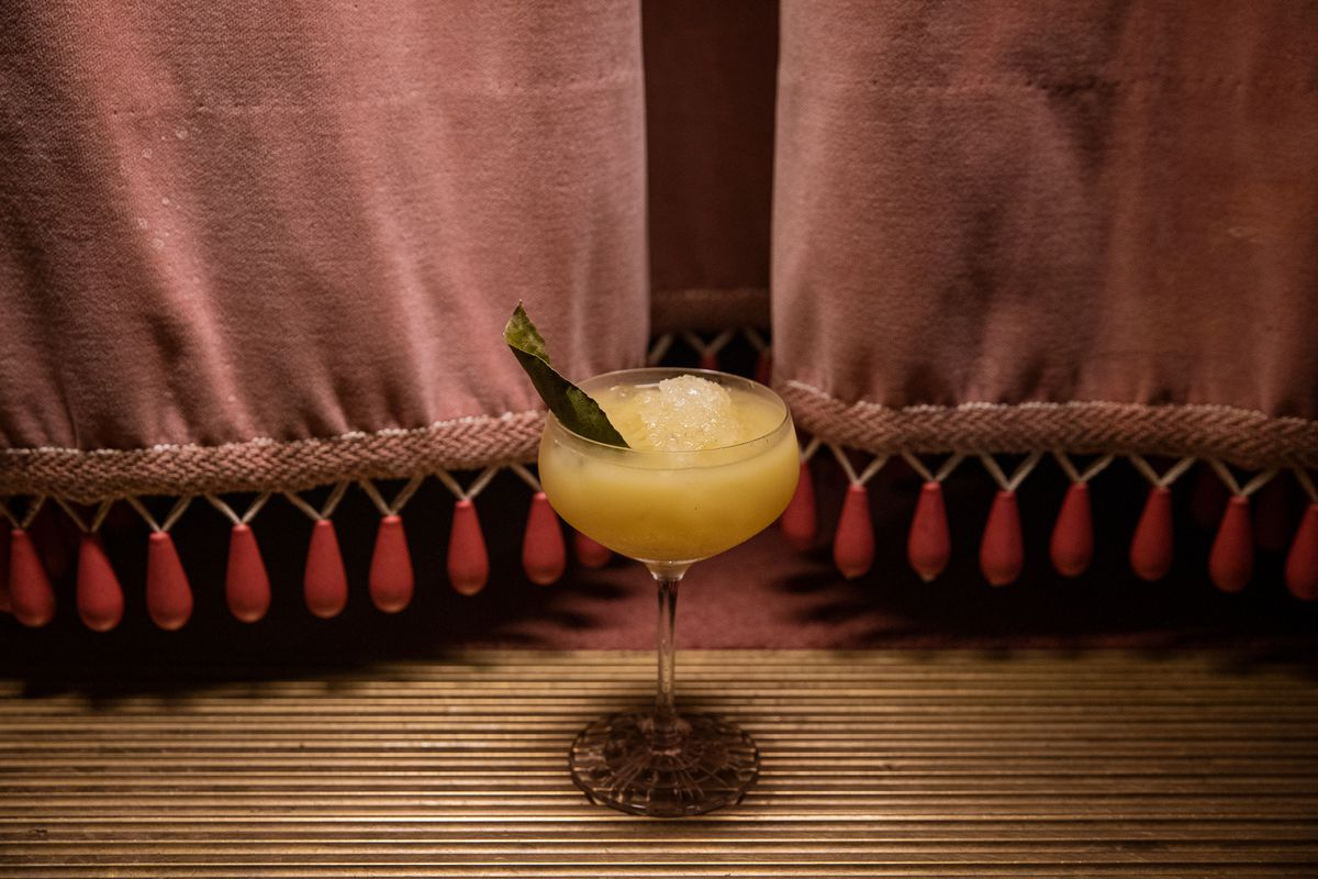 a coup glass filled with a yellow cocktail and a green leaf garnish in front of a pink curtain