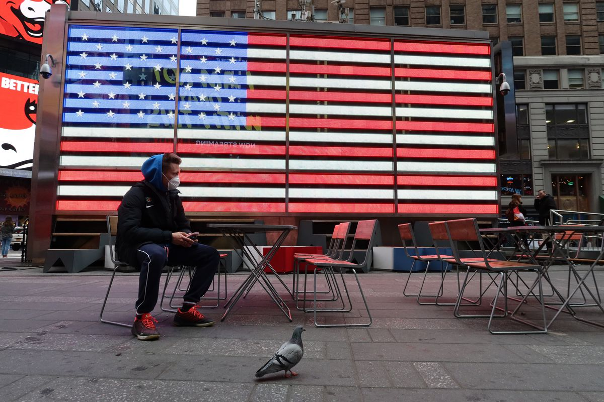 A man wears a protective mask as he sits in Times Square in New York City.