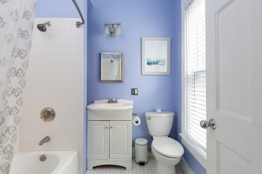 A narrow bathroom with the curtain pulled back on the shower.