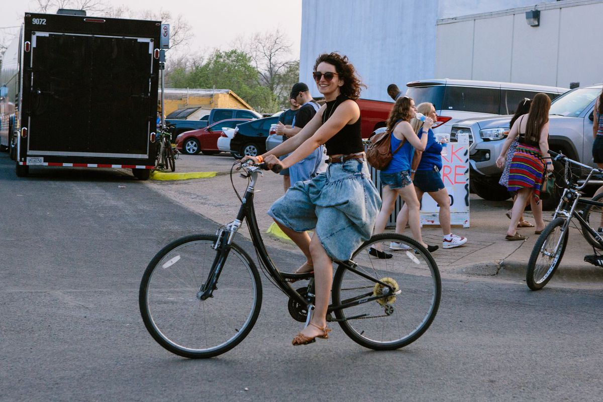 A woman in a black top and denim skirt riding a bike.