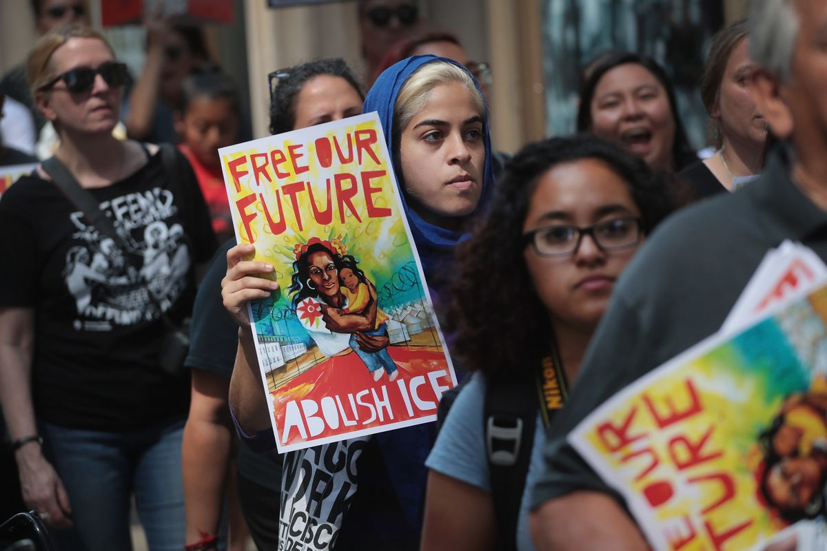 """Protesters, including one holding a sign reading """"Free Our Future: Abolish ICE"""" march in Chicago, Illinois on August 16, 2018."""