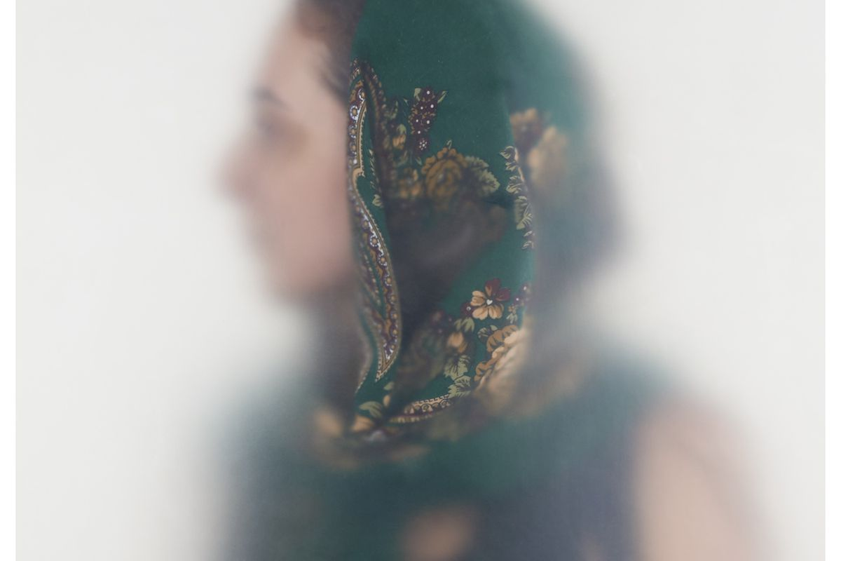 Blurry picture of a woman in a green and gold head scarf