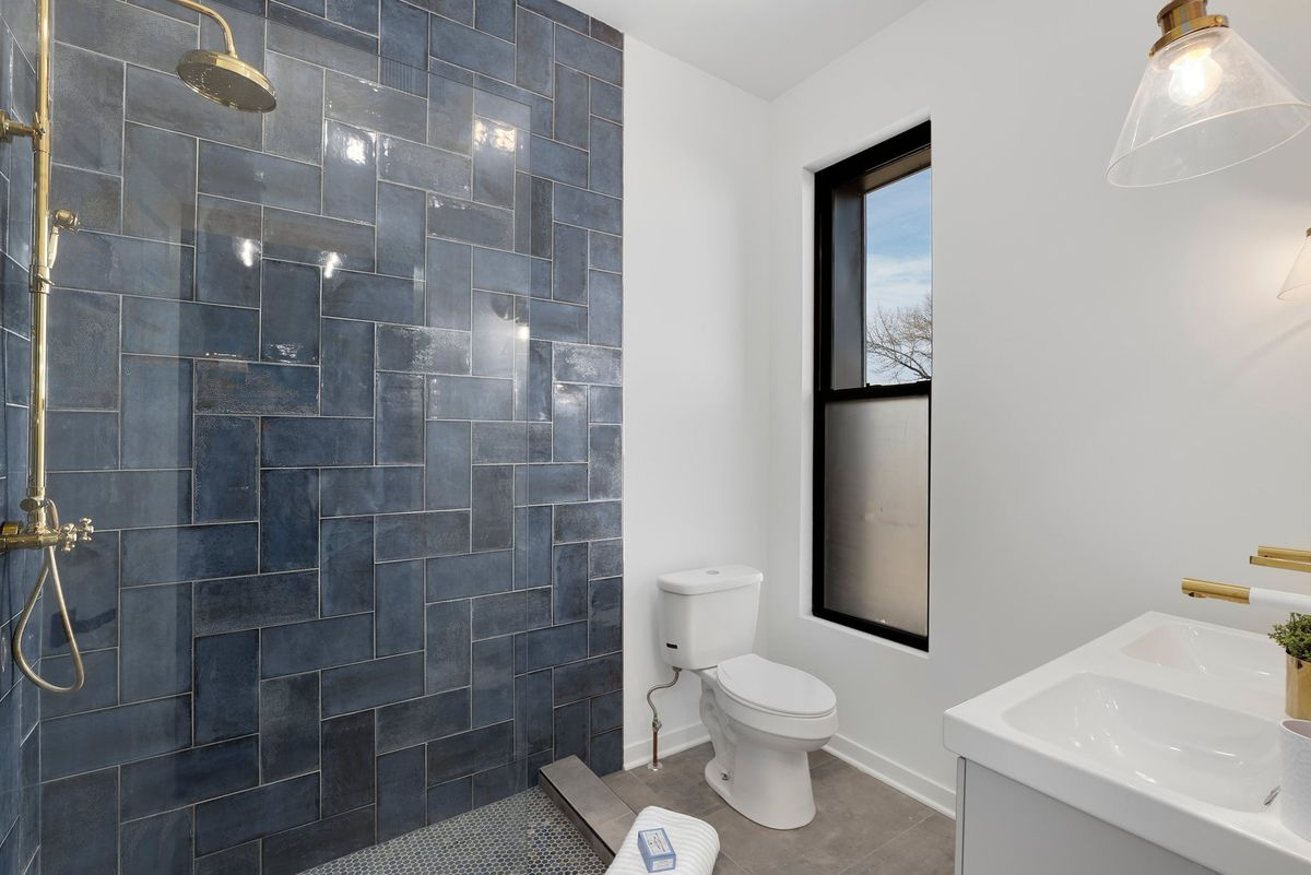 A main bathroom with a glass enclosed shower and double vanity.