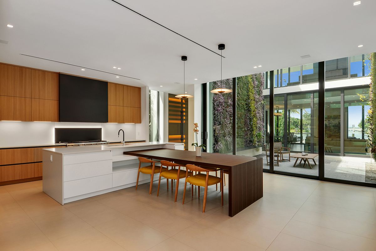 A contemporary kitchen with a large white island, adjoined dinner table, wooden finishes and central atrium next door