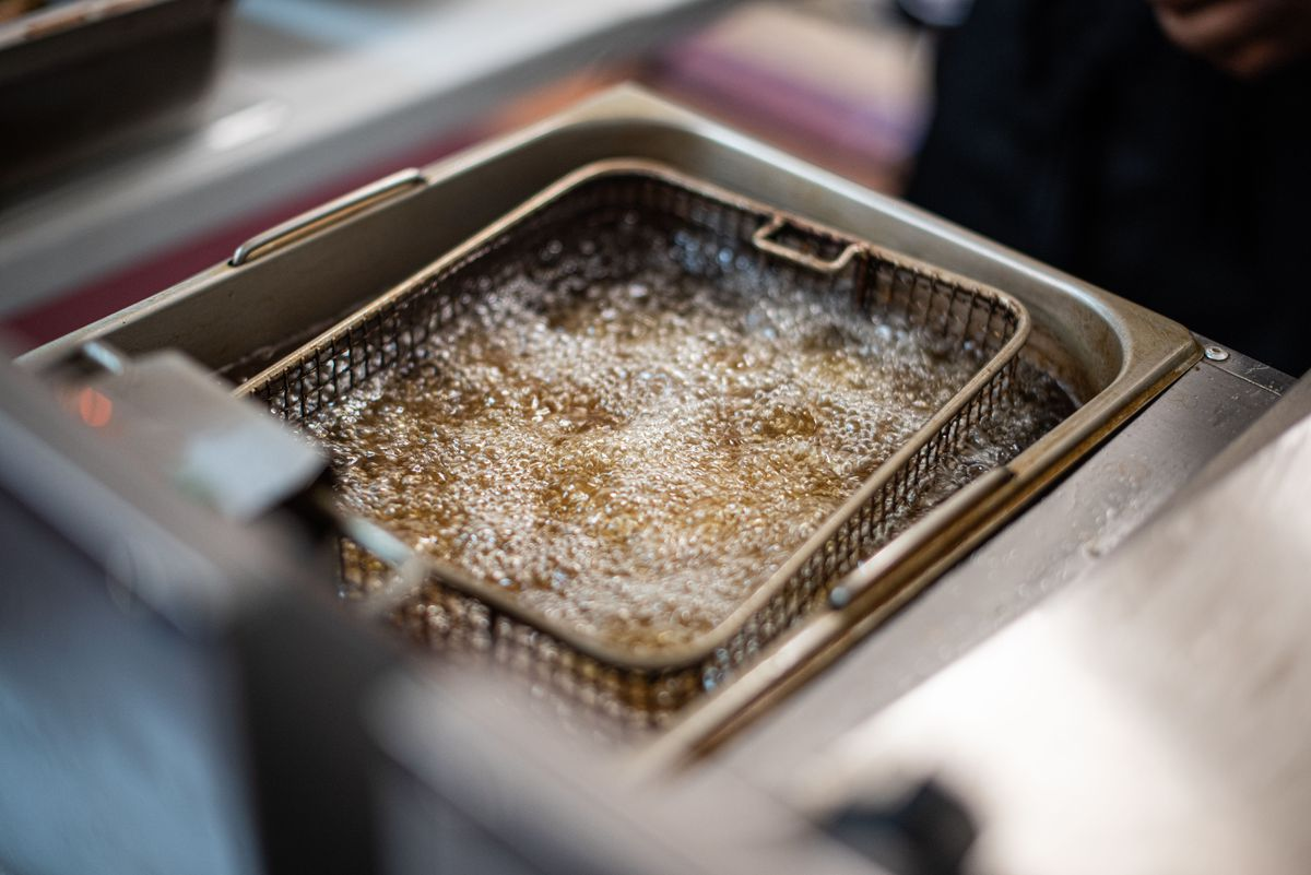 An angled overhead shot of a small fryer cooking wings.