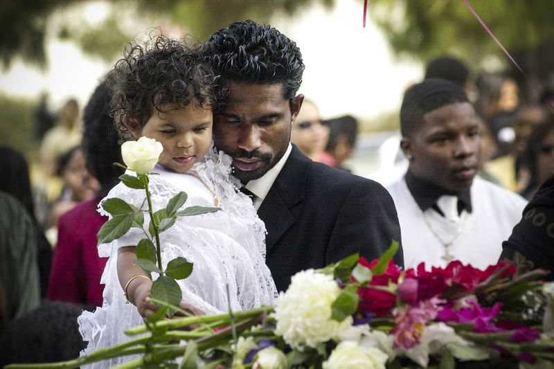 Avinesh Kumar holds his 18 month-old daughter Preshilla, as she places a rose her mother's coffin, during the services for USS Cole sailor Lakiba Nicole Palmer, on October 20, 2000 in San Diego, CA.