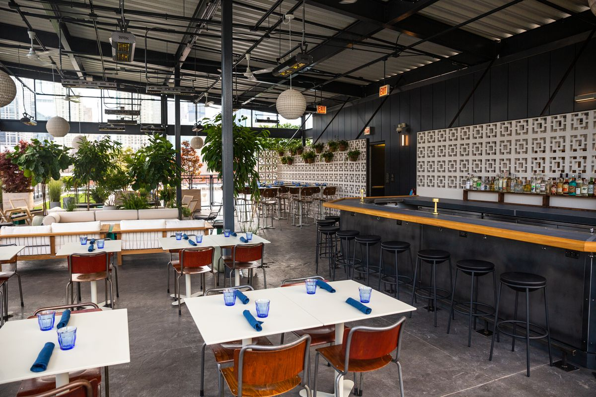 Multiple white tables sit beside a bar under a rooftop overhang.