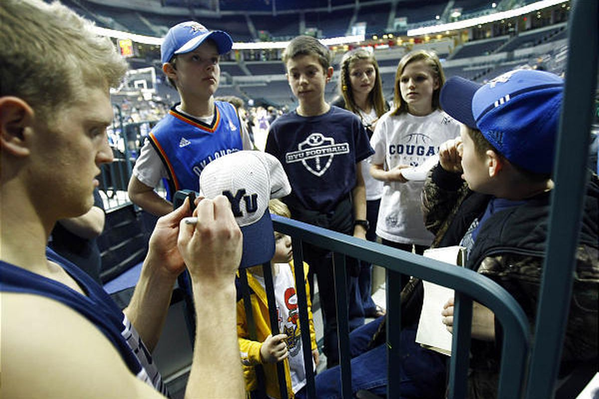 BYU's #23 Tyler Haws signs autographs for a group of kids from Oklahoma after practice.  BYU practiced in the Ford Center in Oklahoma City in preparation for their first round NCAA game against Florida on Thursday.