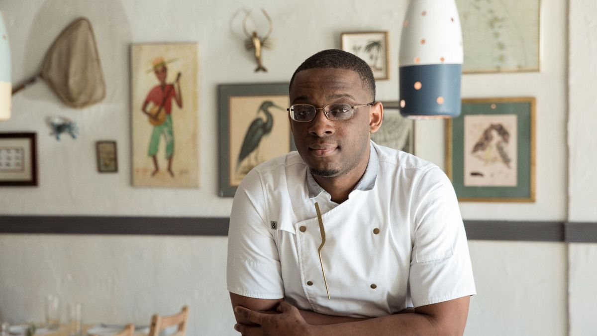 A photo of Cleophus Hethington wearing glasses in his chefs whites and leaning on a table