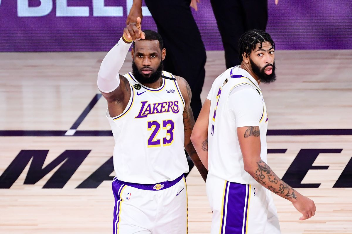 LeBron James of the Los Angeles Lakers and Anthony Davis of the Los Angeles Lakers react during the second quarter against the Miami Heat in Game Six of the 2020 NBA Finals at AdventHealth Arena at the ESPN Wide World Of Sports Complex on October 11, 2020 in Lake Buena Vista, Florida.