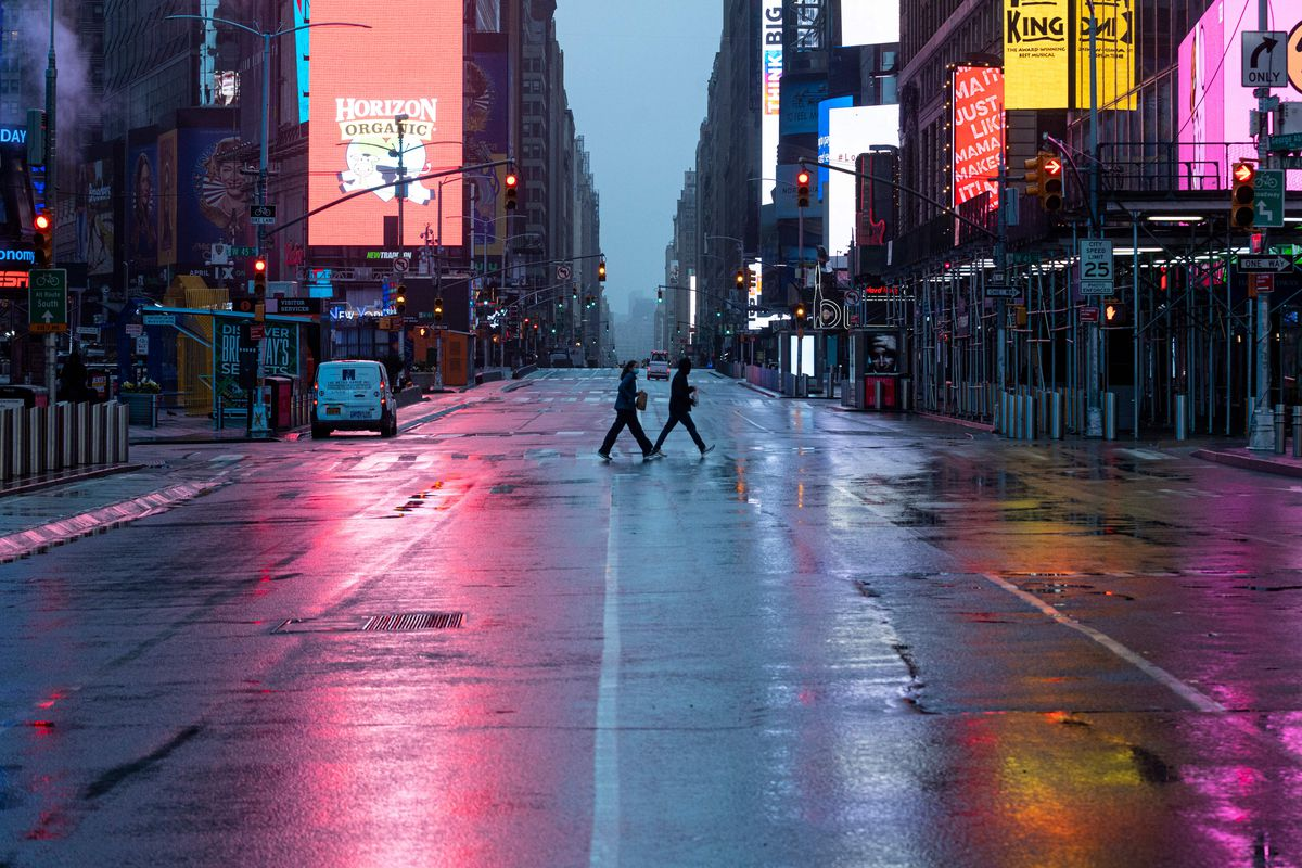A couple walking across Times Square at dusk.