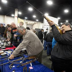 Tim Wilkes, right, sights down the barrel of a hunting rifle at the South Towne Expo Center during the 2013 Rocky Mountain Gun Show, Saturday, Jan. 5, 2013.