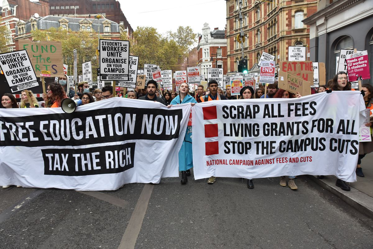 """A large group of students carry banners that read, """"Free education now, tax the rich,"""" and, """"Scrap all fees, living grants for all, stop the campus cuts."""""""