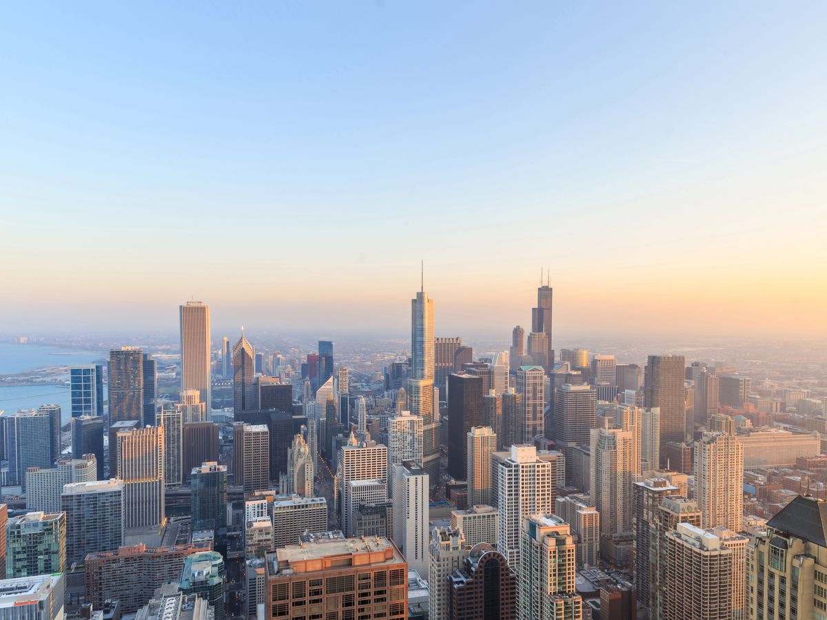 An aerial view of the Chicago cityscape. There are many tall buildings. There is a sunset in the sky.