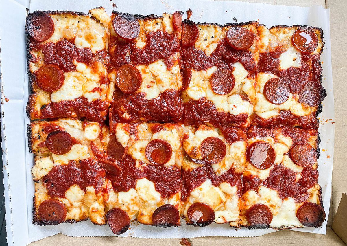 An above shot of a pan pizza with square slices and pepperoni.