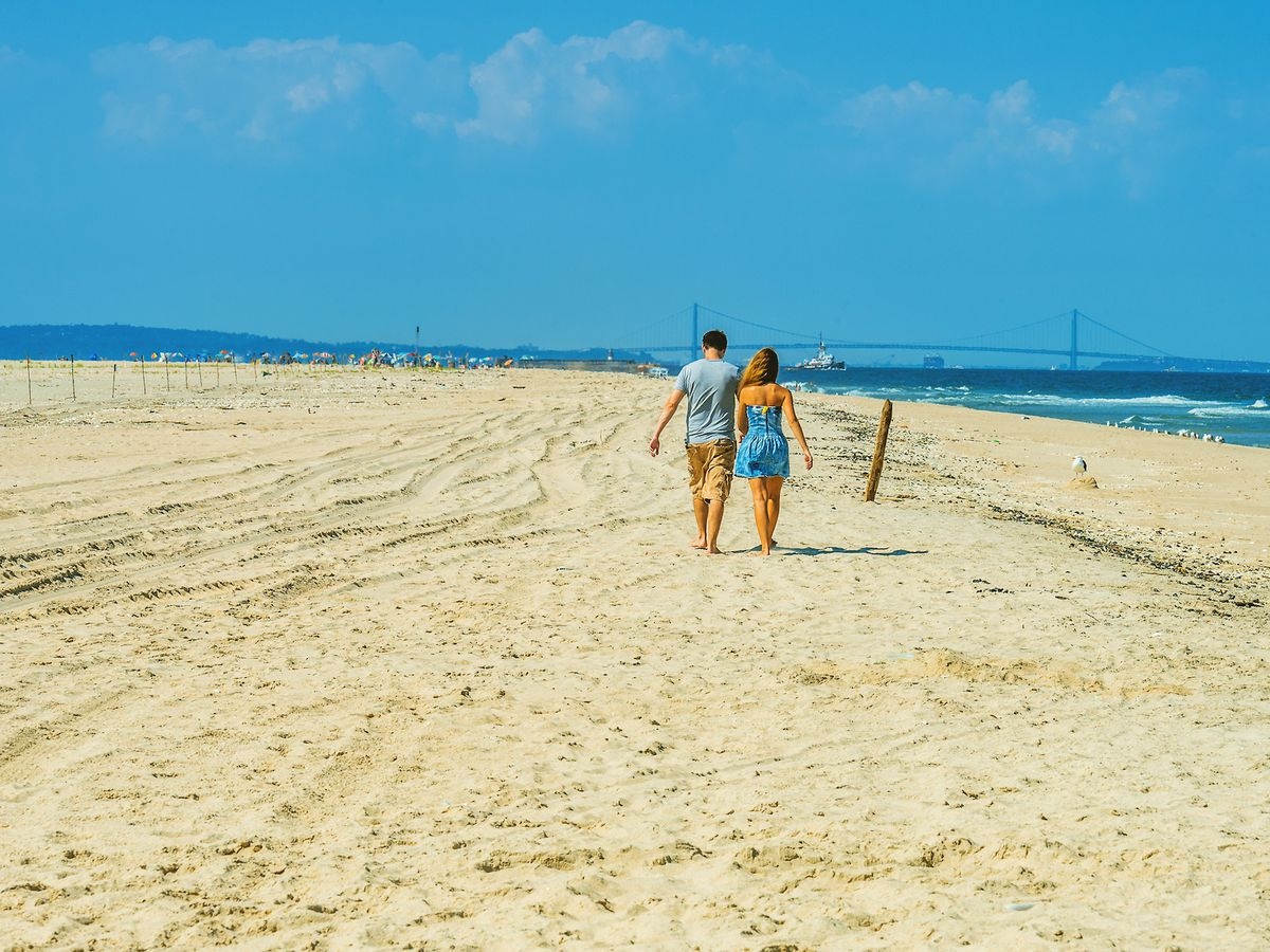 A sandy beach. There is a man and a woman in swimming attire walking along the beach.