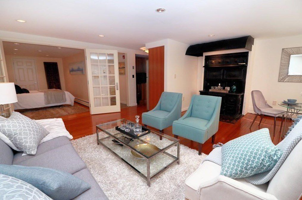 Another angle on that living room, facing toward a bedroom area behind opened French doors.
