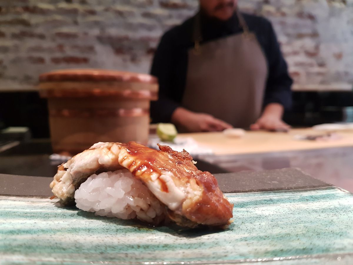 A slice of eel dabbed with sauce atop a clump of sushi rice, with a sushi chef blurred in the background.