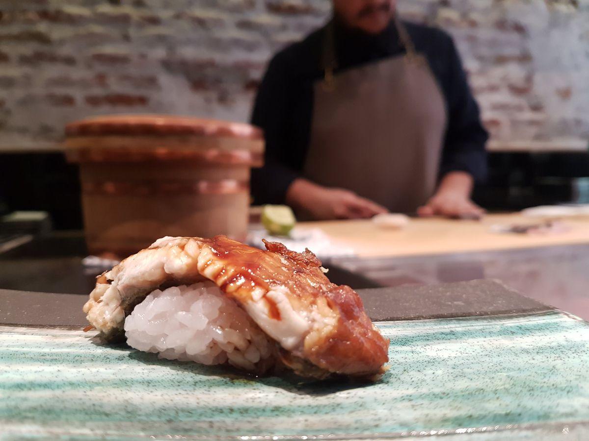 Una rodaja de anguila se frotó con salsa sobre un grupo de arroz de sushi, con un chef de sushi borroso en el fondo.
