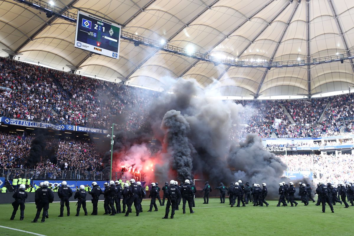 HAMBURG, GERMANY - MAY 12: Police are seen as fans throw flares onto the pitch during the Bundesliga match between Hamburger SV and Borussia Moenchengladbach at Volksparkstadion on May 12, 2018 in Hamburg, Germany.