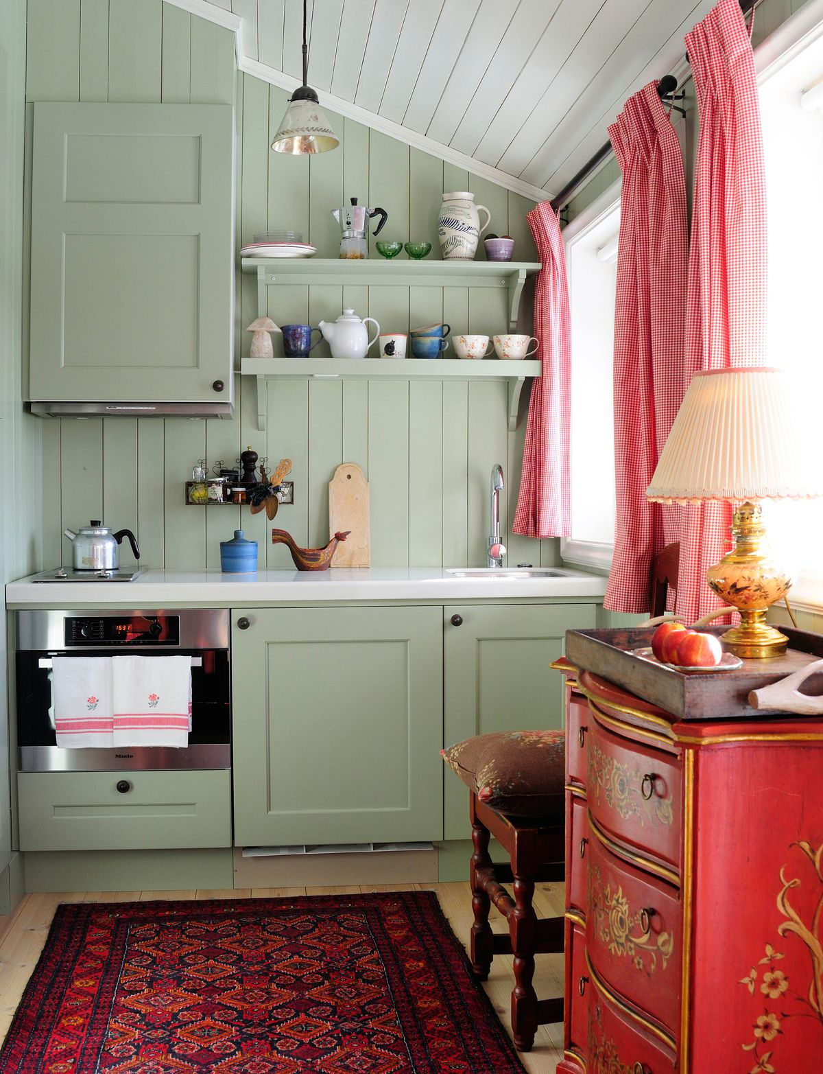 Green kitchen with red furniture and curatins.