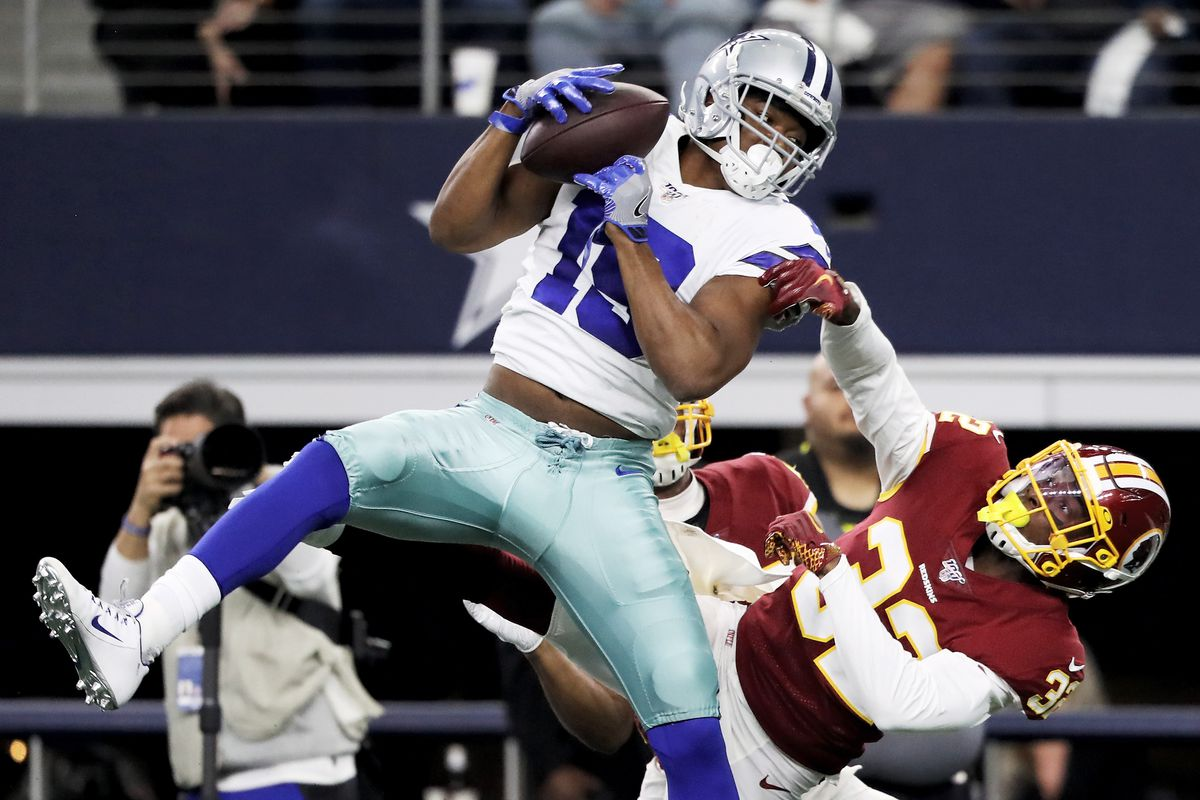 Amari Cooper of the Dallas Cowboys makes a catch while being guarded by Washington's Jimmy Moreland in the second quarter in the game at AT&T Stadium on December 29, 2019 in Arlington, Texas.