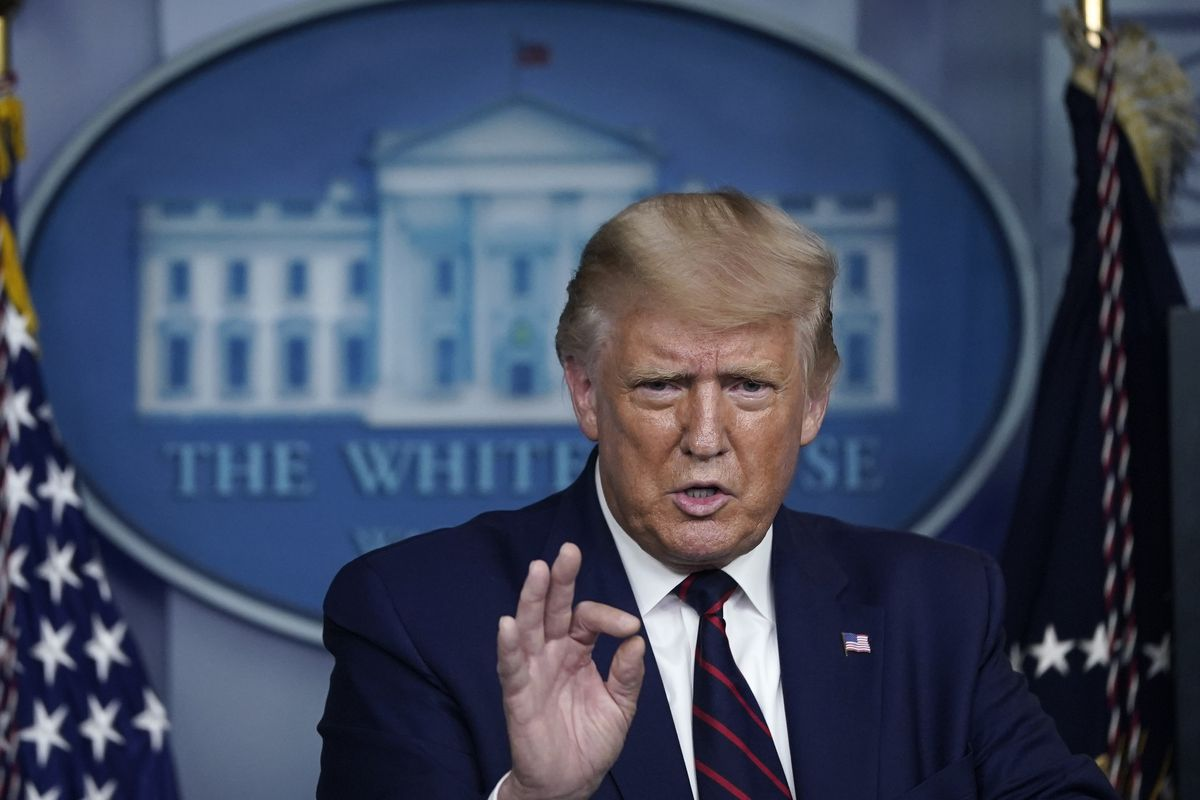 President Donald Trump stands at the podium in the press briefing room of the White House, holding his right hand up and pinching his pointer finger and thumb together as he speaks.