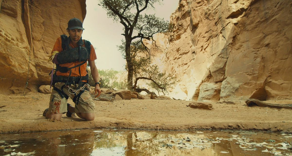 A bloodied, exhausted-looking James Franco, one arm in a sling, kneels by a leaf-covered pond in a rocky valley in 127 Hours.