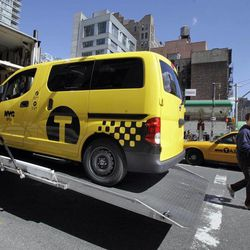 A prototype of the Nissan NV 200 New York City taxi is off-loaded from a truck, in New York, Monday, April 2, 2012. The iconic New York City taxi has gotten a passenger-friendly makeover from Nissan with low-annoyance horns, USB chargers and germ-fighting seats to cut down on bad odors. Medallion owners will be required to buy the Nissan NV 200 at a cost of about $29,000 starting in late 2013.