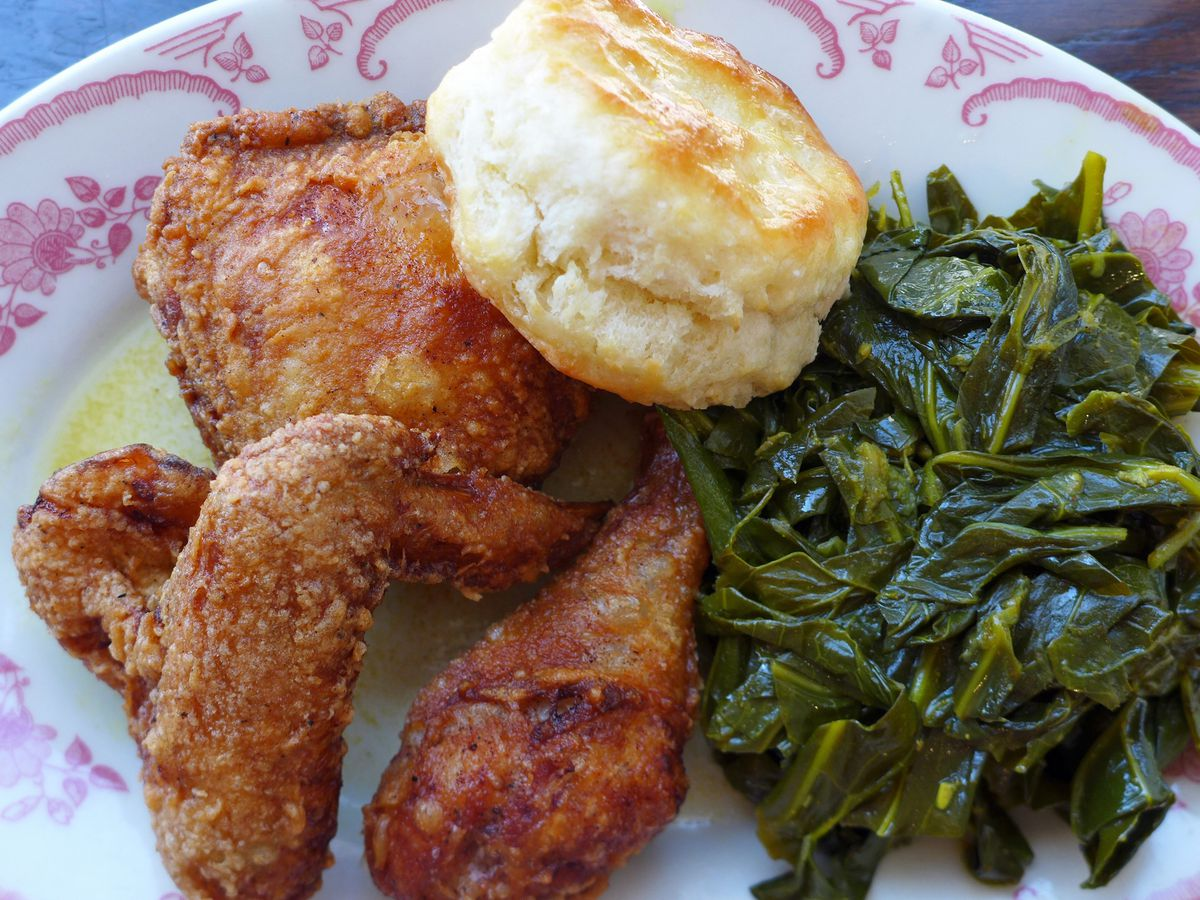 Fried chicken with collard greens and a biscuit on a pink flowered plate