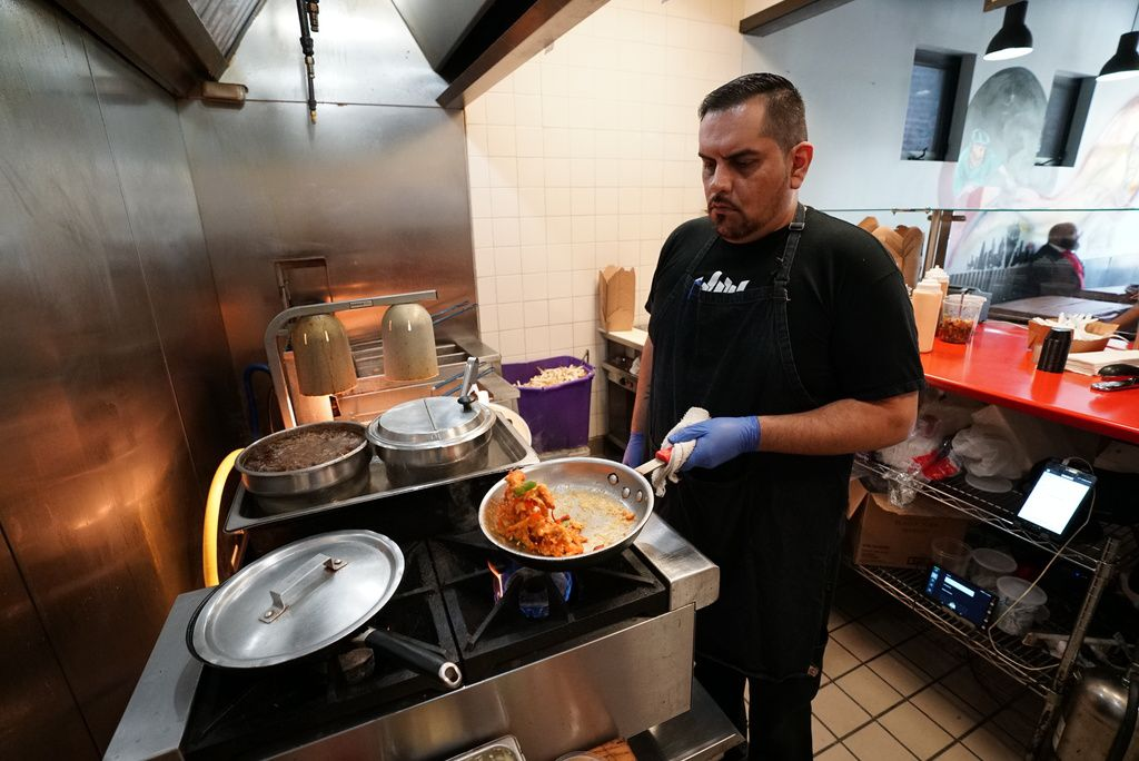 Oscar Cardona, the chef at Friistyle, sauteing lobster, celery, and red peppers for the lobster frite