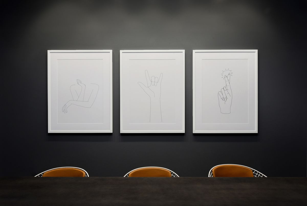 A black wall with three figurative drawings on white paper above a table and three curved chair backs.