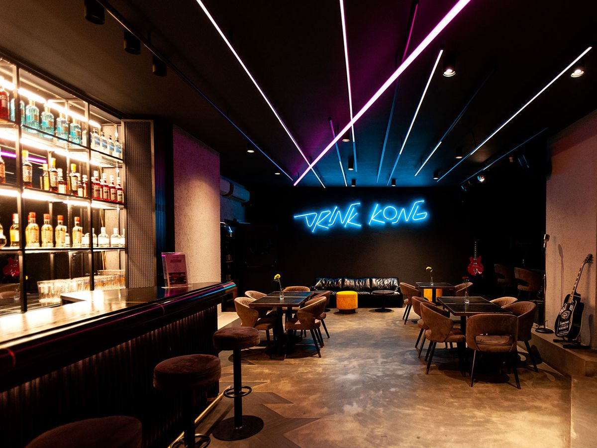 """A bar interior, with a brightly lit bar, tables and lounge area, cement floor, bright strip lighting on the ceiling, and neon sign reading """"drink kong"""" on the far wall"""