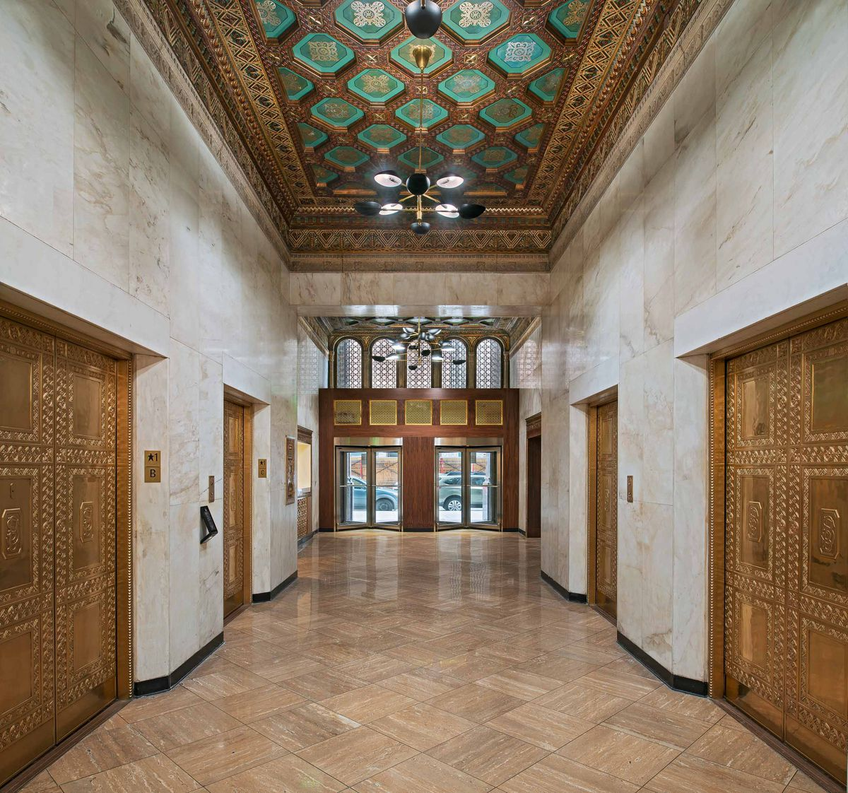 A hallway with four golden elevators on a brown marble floor with white marble walls. Above is a green- and gold-paneled ceiling.
