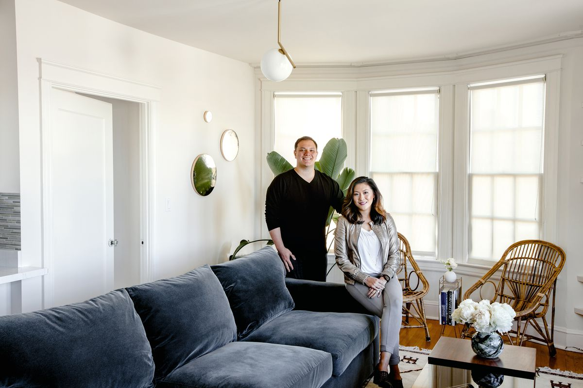 Niles Lichtenstein and Alicia Cheung Lichtenstein sit in their living room. The white room has a blue-gray sofa and a pair of light-colored rattan chairs.