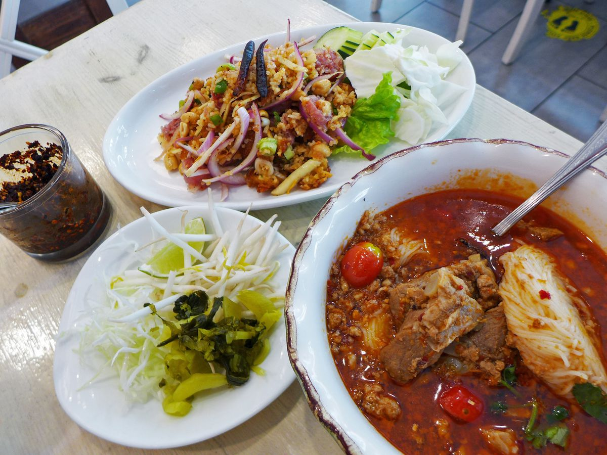 A place of rice salad and bowl of red soup, with garnishes that include sprouts and pickled mustard greens served separately.
