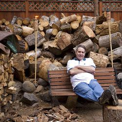 Homeowner Christopher Paulsen sits in front of the woodpile he and his roommate are chopping for winter at Paulsen's home in Incline Village, Nev.