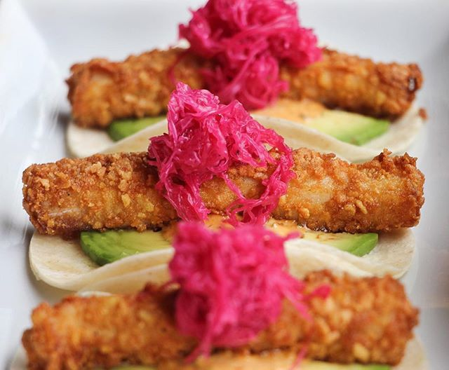 Three corn tortillas with sliced avocado, long tubular fried potato or fish and a pile of pickled pink onion on top.