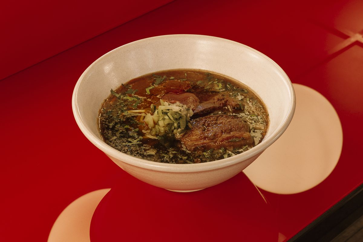 A bowl of Taiwanese beef noodle soup on the red bar at Bao's new Shoreditch restaurant