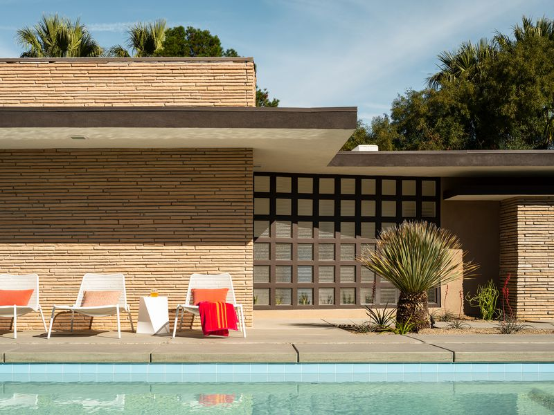 A pool sits next to a flat-roofed house, with white chairs and red pillows sitting next to it.