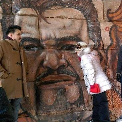 """Artists painted a mural near 22nd and Central Park featuring """"Pastor Vic."""" His wife Magdalena admires the mural from the right. 