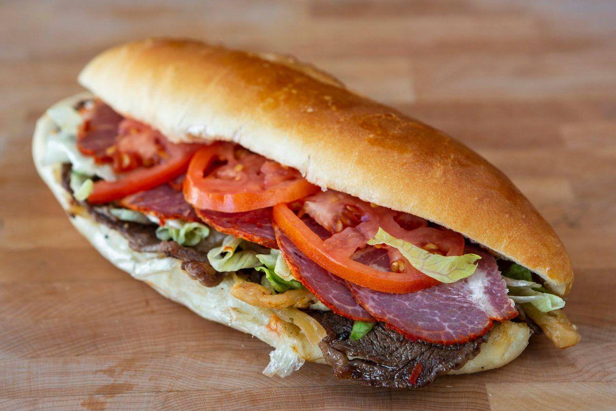 A steak-capicollo sandwich with lettuce and tomato on a long bun.