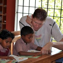 Former NBA player Shawn Bradley helps children with their studies at the Rising Star Outreach campus in Thottanaval, India.